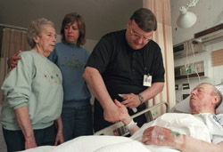Franciscan Father Anthony Janik, chaplain at St. Anthony Medical Center in Crown Point, Ind., anoints the hands of George Schmidt May 23 as his wife, Irene, and daughter, Andrea Fox, look on. In a recent survey, chaplains said priests often are not available when needed for the sacrament of anointing of the sick. (CNS photo by Karen Callaway, Northwest Indiana Catholic) (May 24, 2001) See ANOINT May 22, 2001.